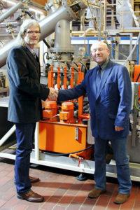 Dr.-Ing. Michael Müller (links) und Professor Dr.-Ing. Bohumil Kasal (rechts) vor dem Refiner des Fraunhofer WKI. © Fraunhofer WKI